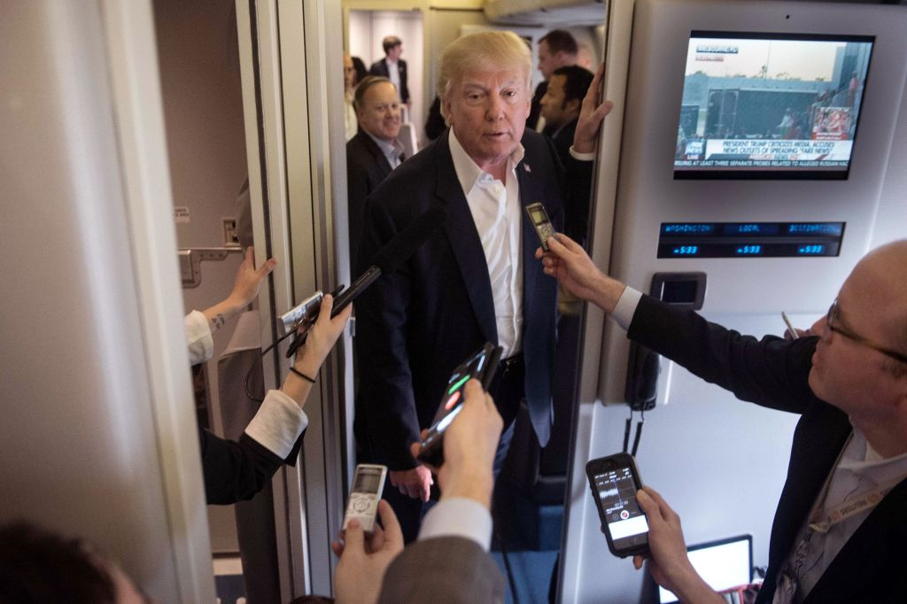 US President Donald Trump speaks to the press aboard Air Force One