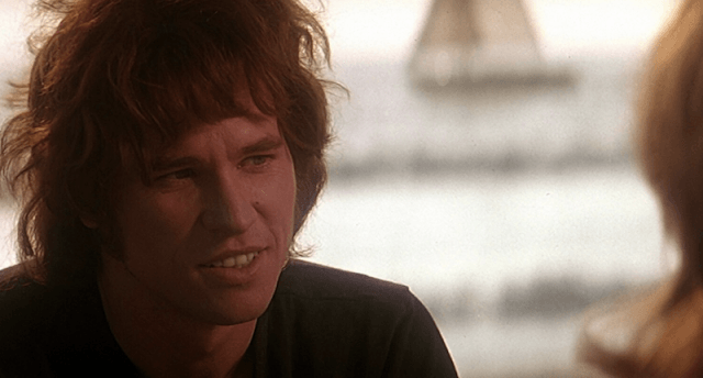 Val Kimer in 'The Doors' speaking to a woman.