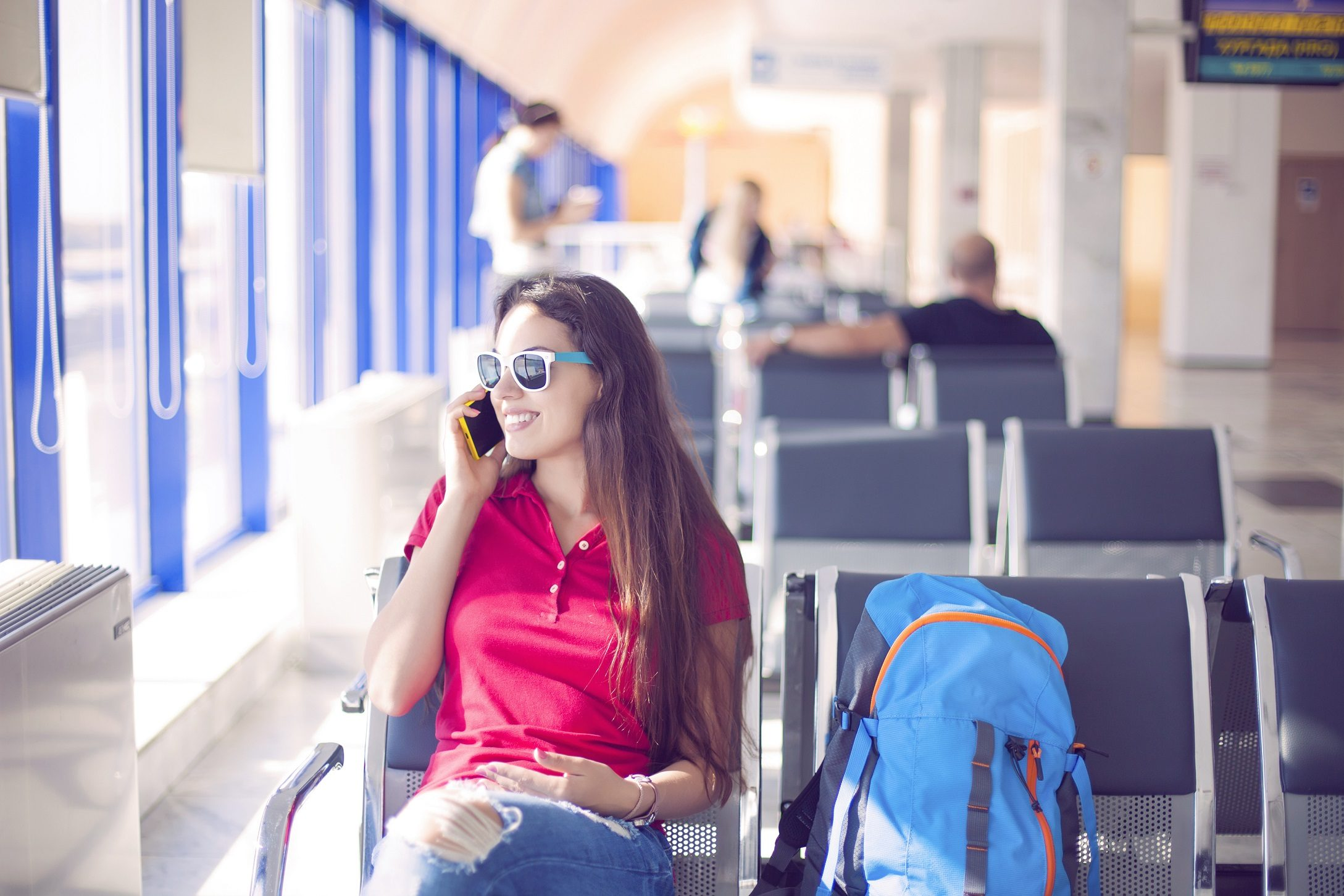 Young female passenger on smart phone at airport
