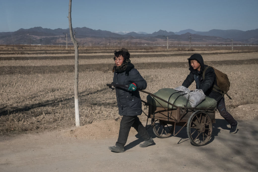 A woman and child pull a cart loaded with wood along a road near Kiliju on North Korea's northeast coast