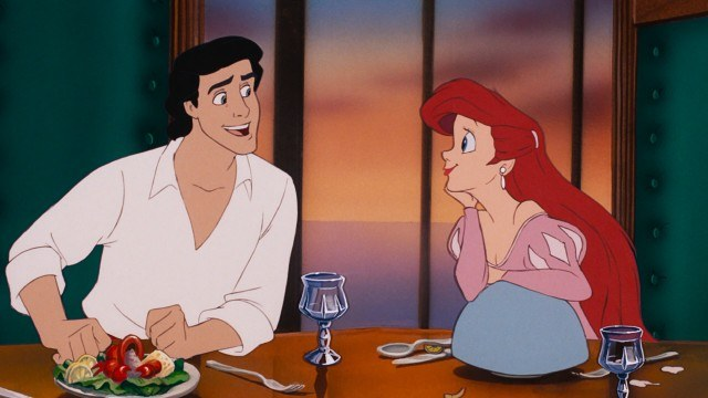 Ariel looks at Prince Eric with stuffed crab on his plate in The Little Mermaid