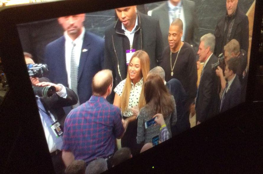 A monitor showing Beyoncé and JAY-Z shaking hands with Prince William and Kate Middleton