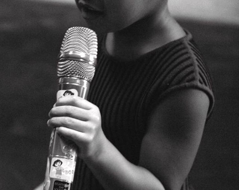 Blue holds a microphone
