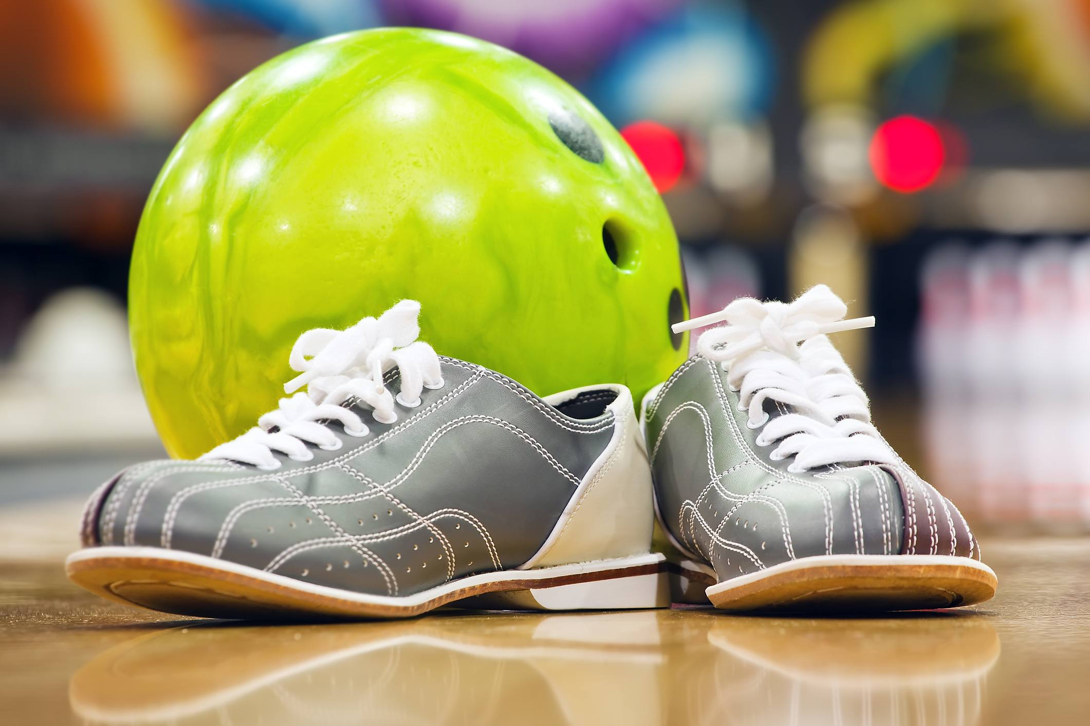 Close-up of bowling shoes and neon green ball