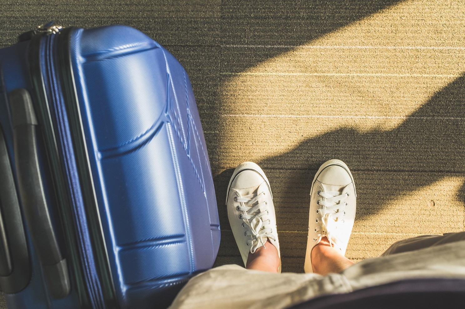 Aerial view,Looking down at white sneaker and travel suitcase with morning sunlight through window at airport terminal,Vacation concept