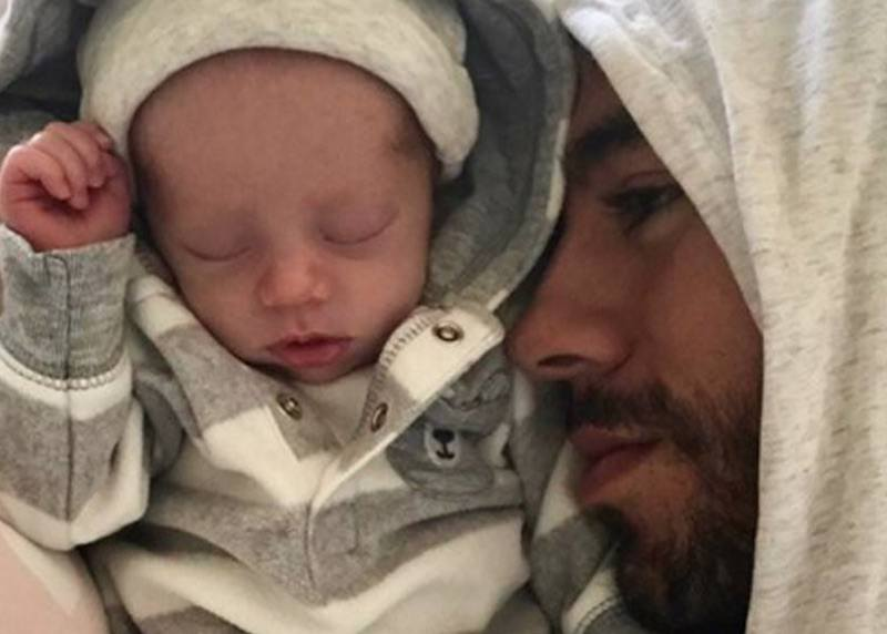 Enrique Iglesias cuddles with his newborn