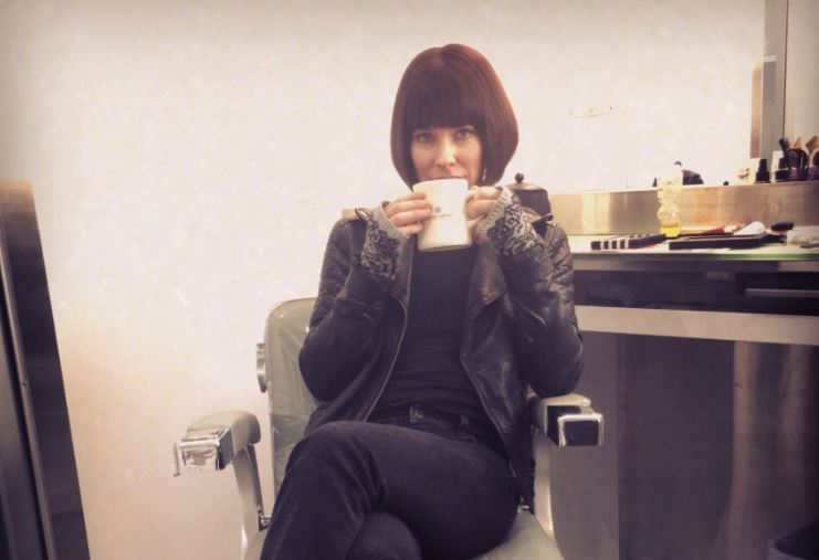 Evangeline Lilly sitting in a chair holding a mug.
