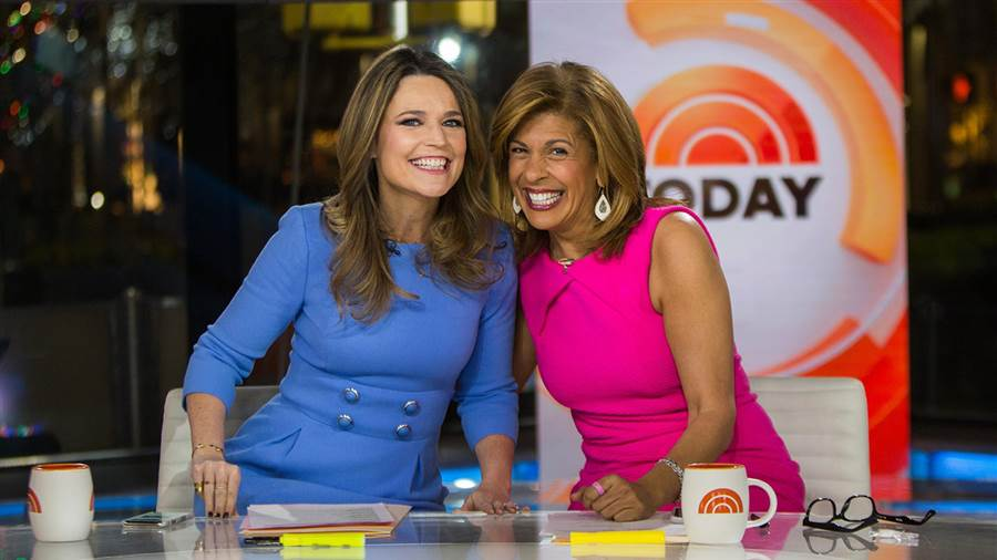 Hoda Kotb and Savannah Guthrie smiling while sitting behind the 'Today' desk.