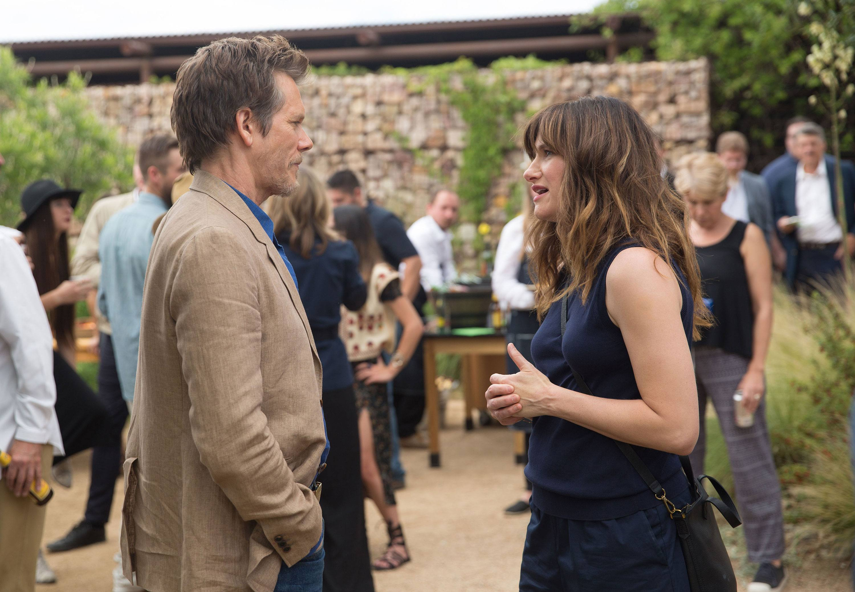 Kathryn Hahn and Kevin Bacon stand and look at each other