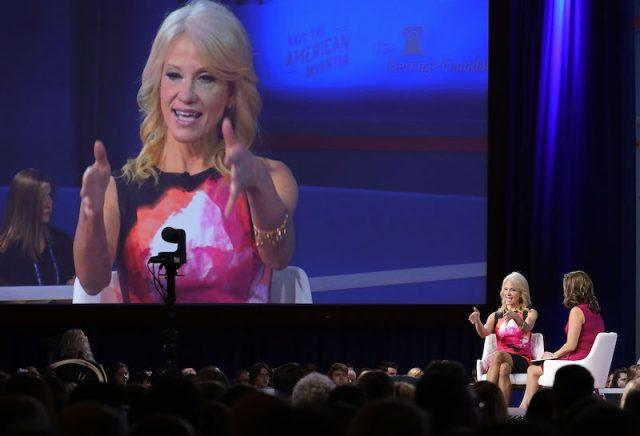 Kellyanne Conway sitting on stage while the screen projects her movements.