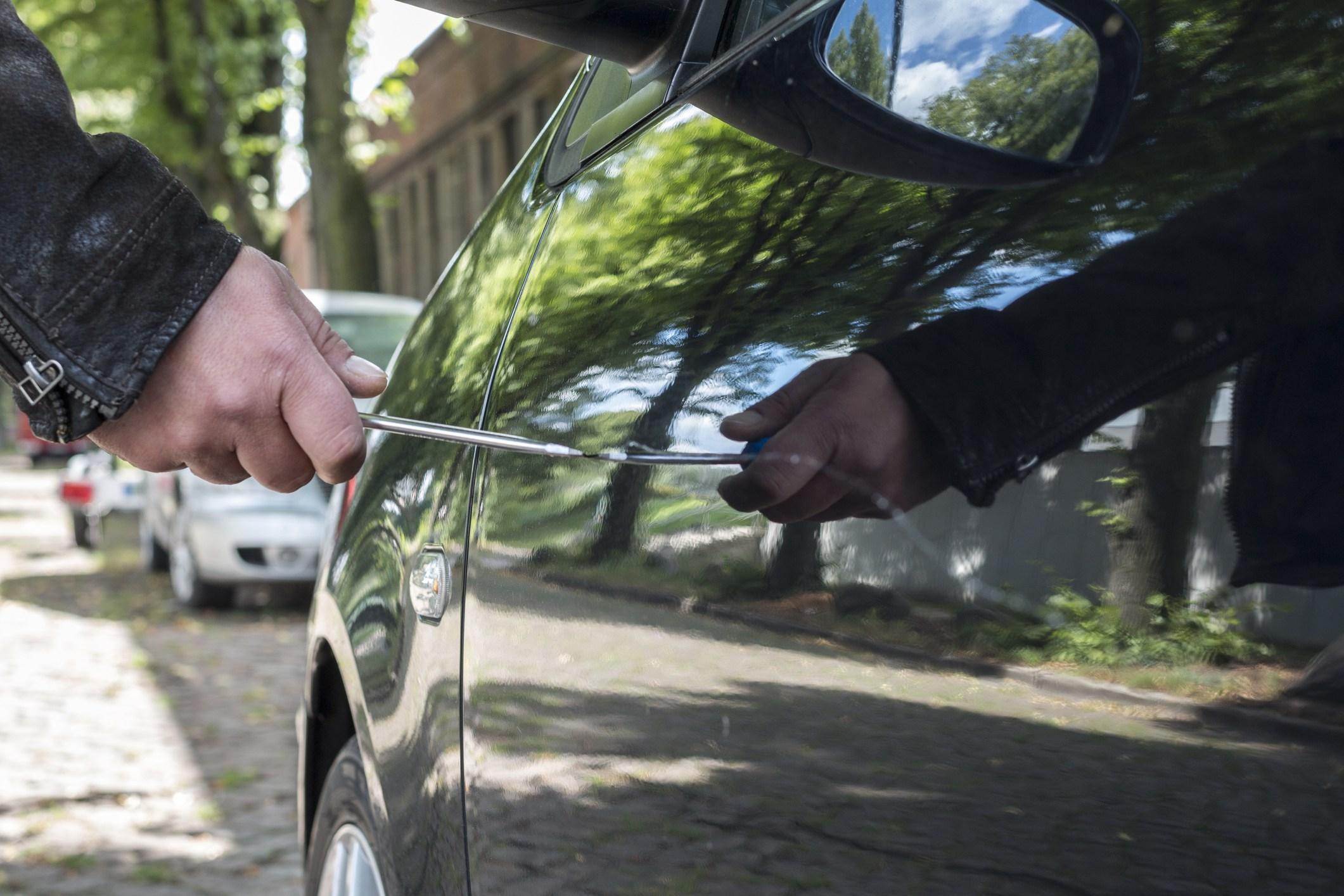 A person vandalizing a car