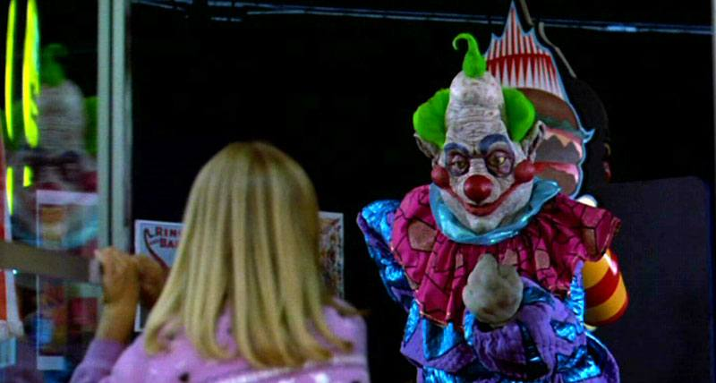 A scary clown looks at a blonde child
