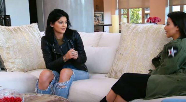 Kylie Jenner and Kim Kardashian sitting on a couch on 'Keeping Up with the Kardashians'.