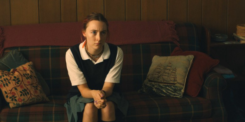 Saoirse Ronan sits on a plaid couch