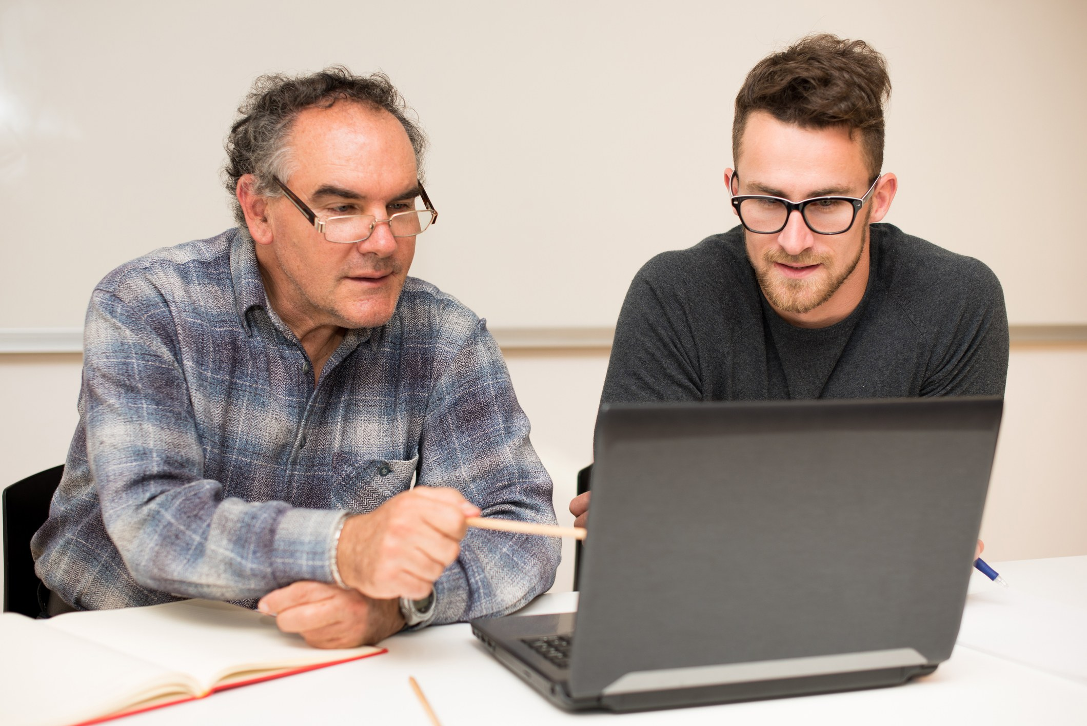 Mature tutor teaching young man on the computer