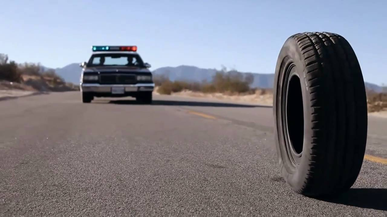 a rubber tire on a road behind a cop car