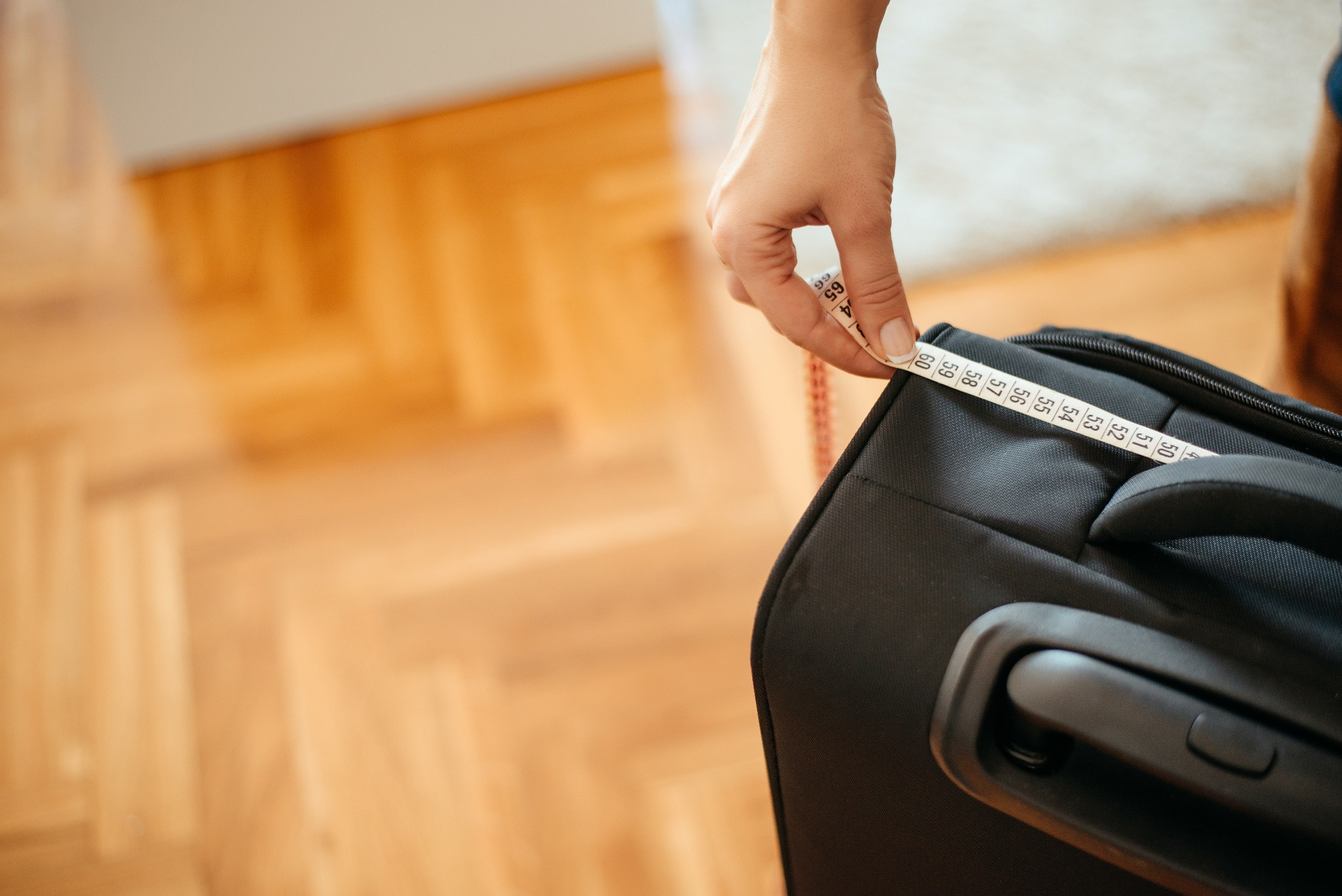 Close up woman hand using measuring tape on a suitcase