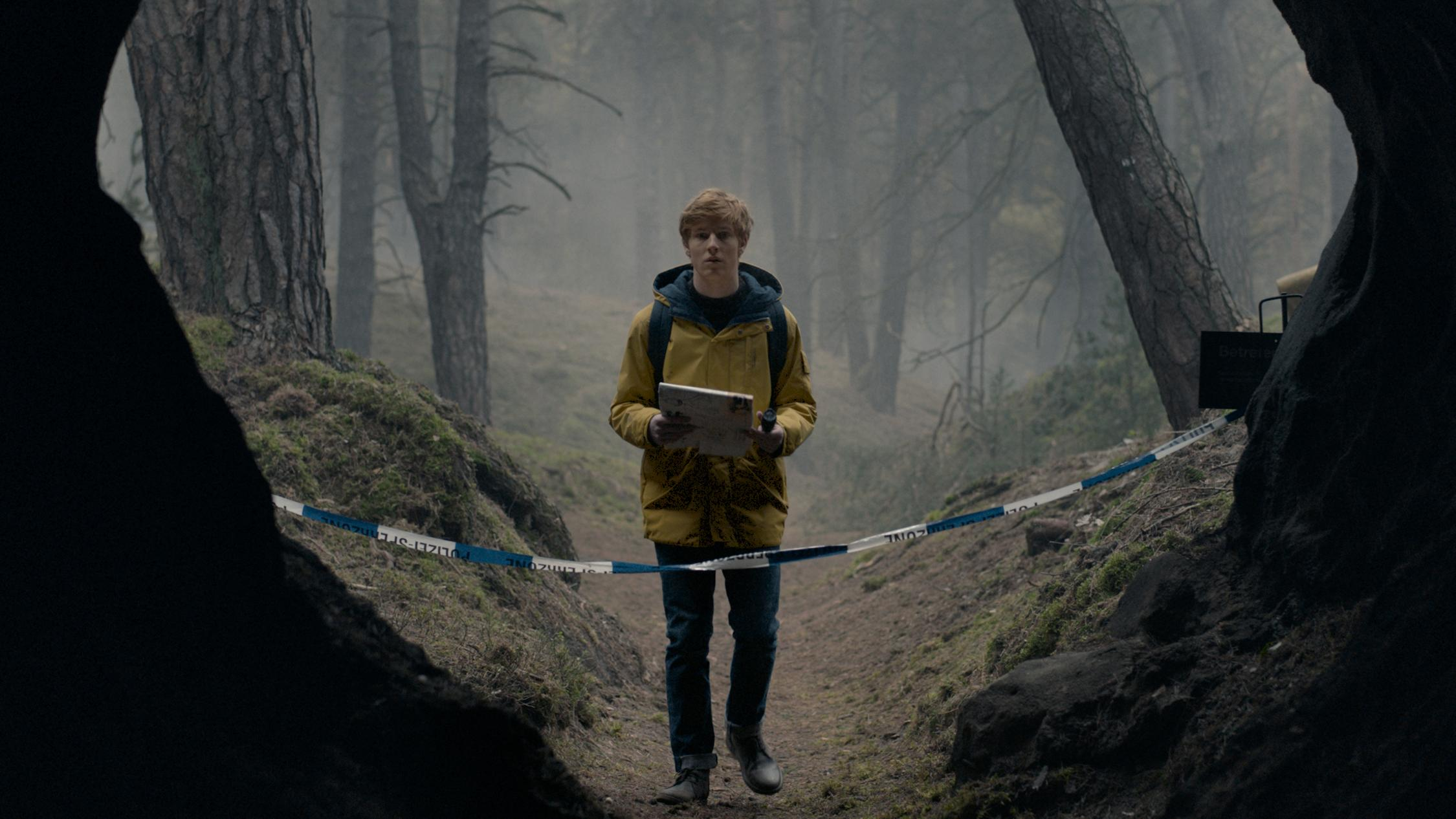 A boy stands in woods