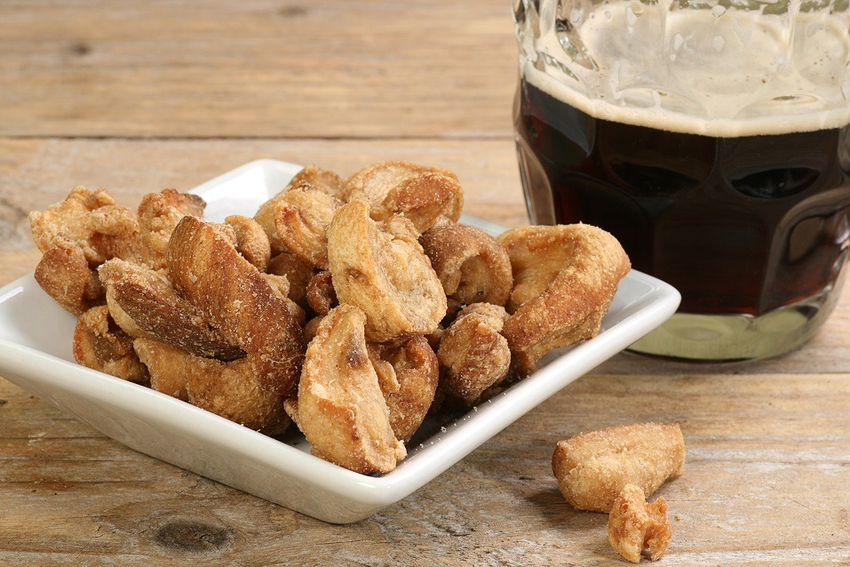 Traditional english midland snack of salted pork scratchings with a pint of beer