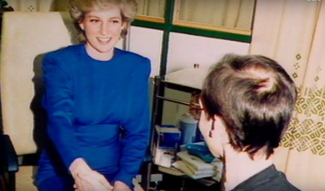 Princess Diana sitting on a beige sofa while greeting another person.