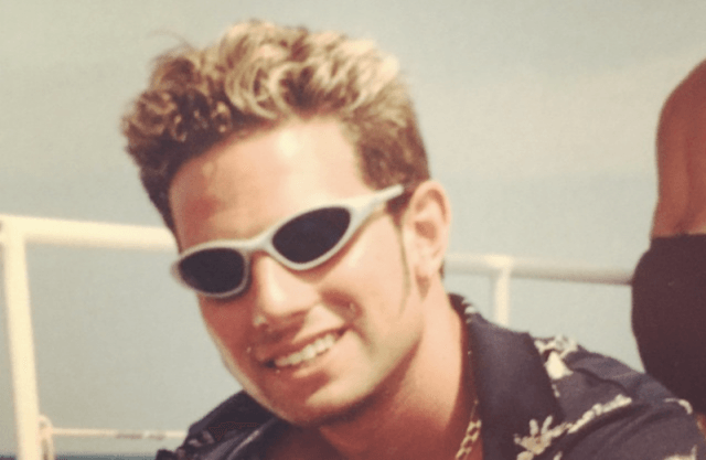 Scott lounging on a boat while wearing sunglasses.