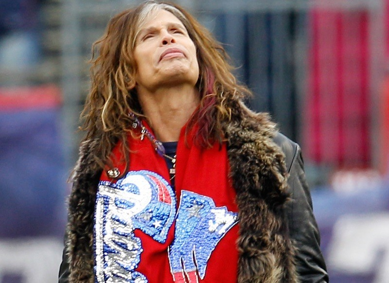 Steven Tyler looks up while wearing a red patriots scarf