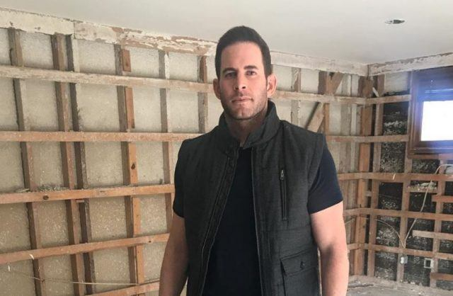 Tarek El Moussa posing in front of a house that is being constructed.