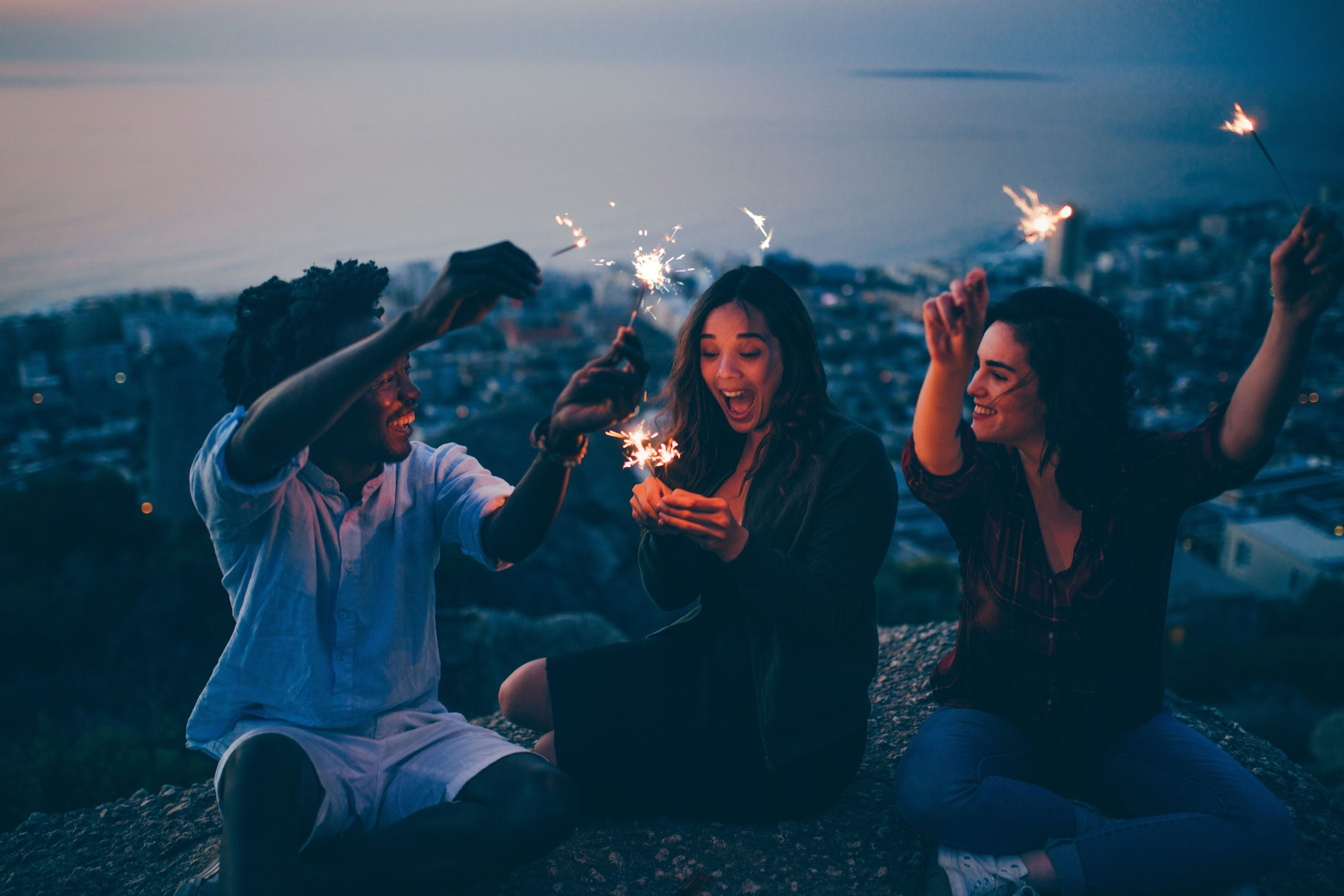 Group of friends celebrating with sparklers at night