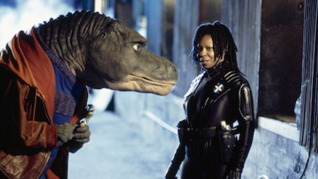 Whoopi Goldberg stands in front of a dinosaur