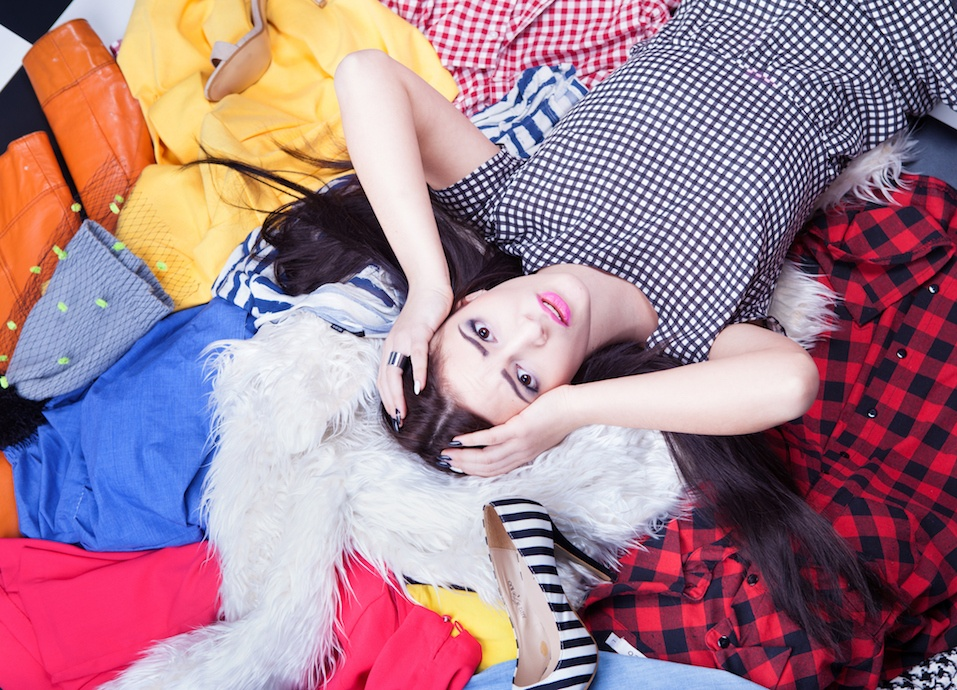 Young attractive stressed woman lying down on a pile of clothes