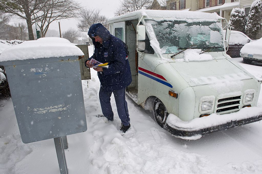 A US Postal Service carrier delivers mail during a snow storm.