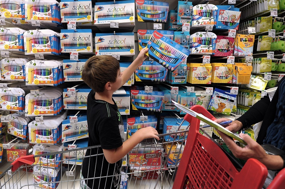 A boy holds pencils at a supermarket of Strasbourg