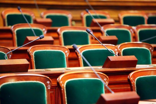 Seats, microphones and tables inside a room.