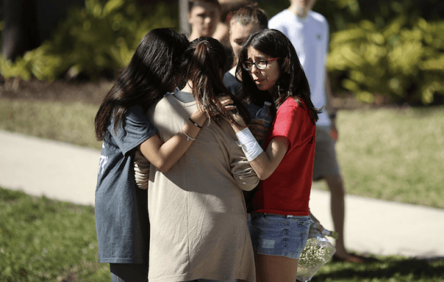 A group of students comforting each other.