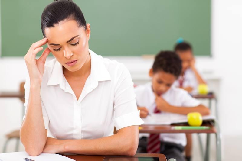 primary teacher having headache in classroom