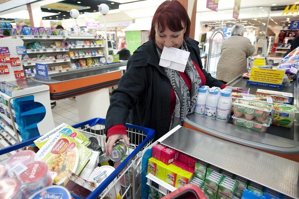 A woman holds her shopping list with her teeth