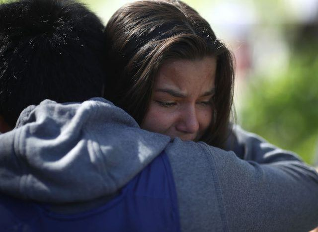 A young woman is hugged as she cries.