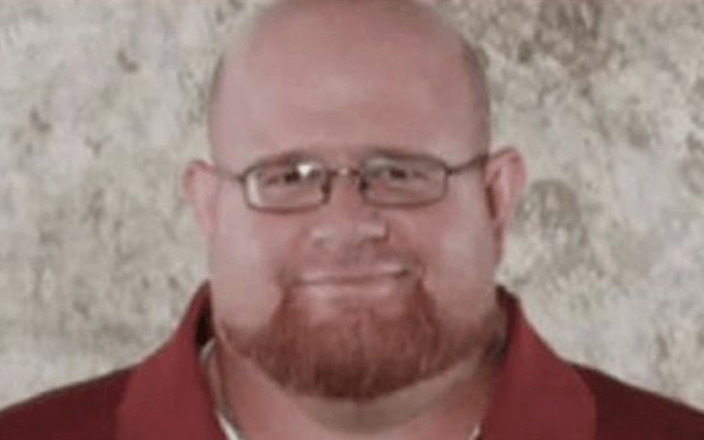Aaron Feis smiling while wearing a red shirt and glasses.