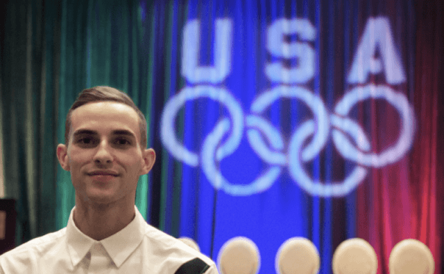 Adam Rippon posing in front of a curtain.