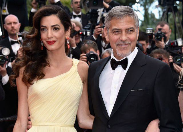 Amal Clooney holding George Clooney's back.