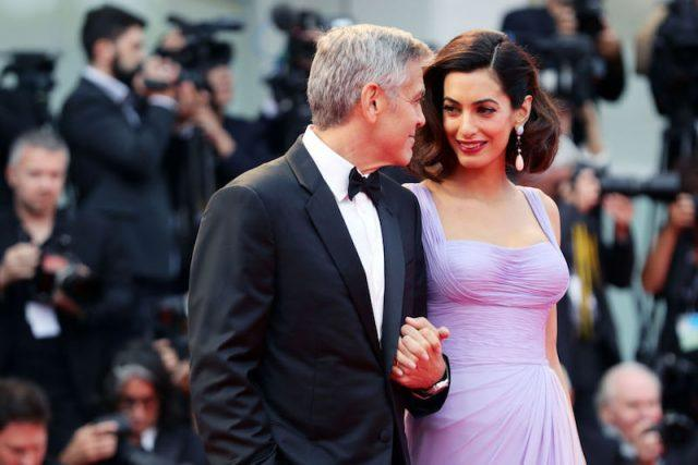 George Clooney holding hands with Amal.