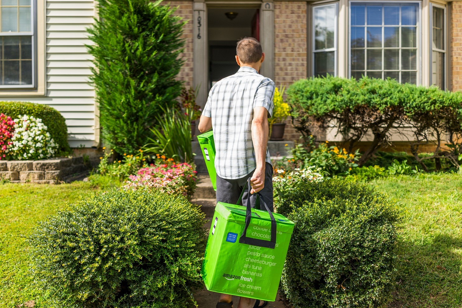 Amazon Fresh insulated grocery delivery bags totes on front home house porch closeup with man carrying