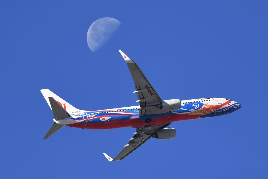 An Air China plane flies in front of the moon