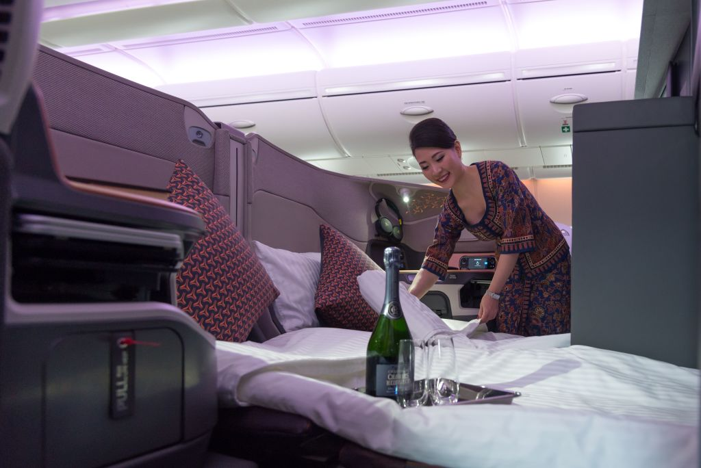 An air stewardess arranges bedsheets of a double bed