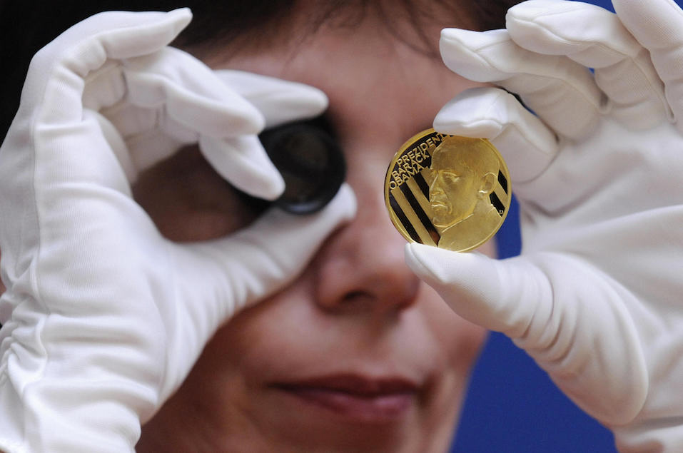 An employee of the Jablonex mint factory checks the quality of a commemorative gold medal