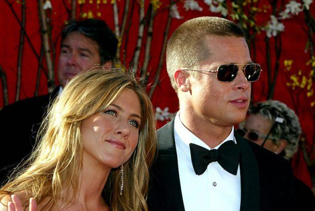 Jennifer Aniston smiling and waving as she poses with Brad Pitt.