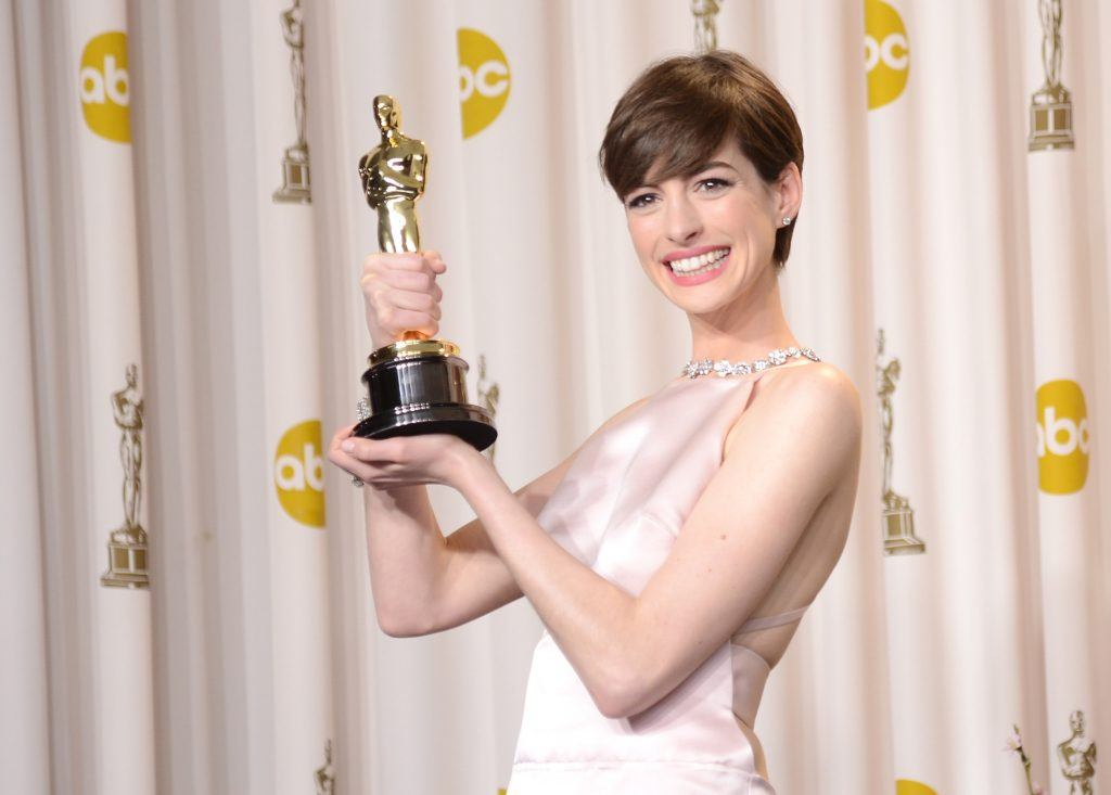 Anne Hathaway holding her oscar