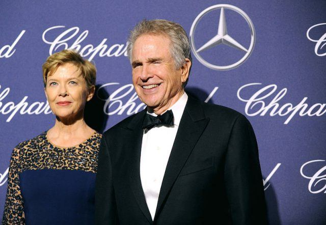 Annette Bening and Warren Beatty smiling in front of a blue backdrop.