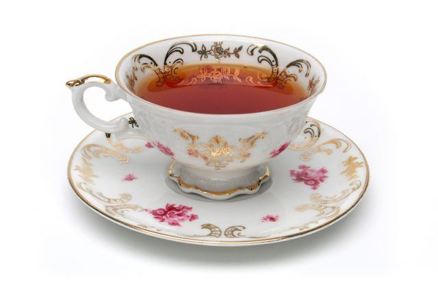 An antique tea cup on a white background.
