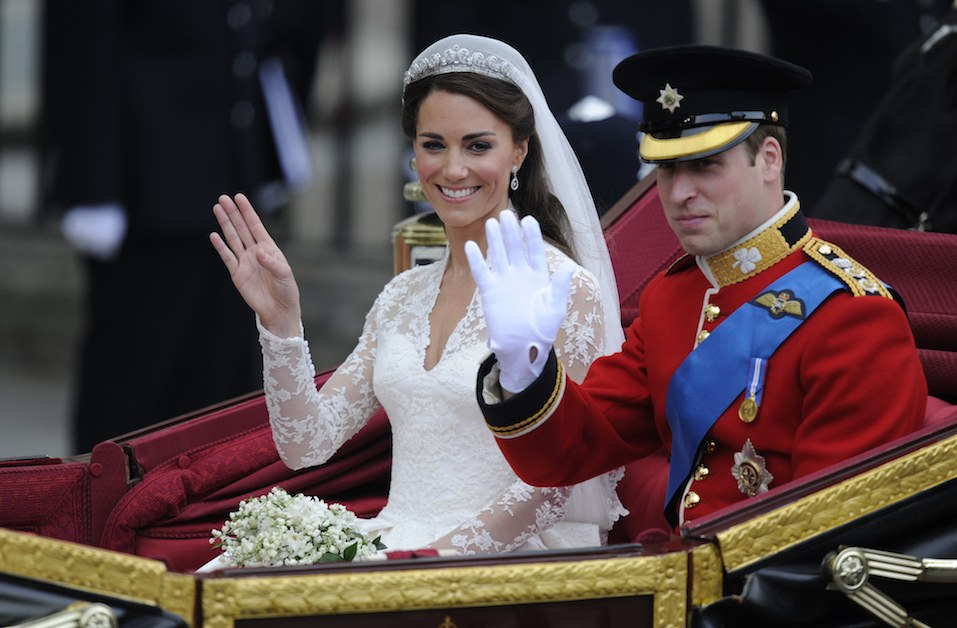 Britain's Prince William and his wife Kate, Duchess of Cambridge, wave as they travel in the 1902 State Landau carriage